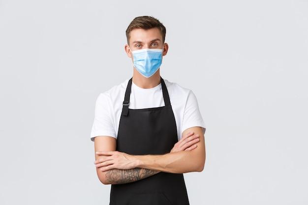 Coronavirus, distanciation sociale dans les cafés et restaurants, affaires pendant le concept de pandémie. beau barista, vendeur d'un petit magasin de détail en tablier noir et masque médical saluant les invités du café