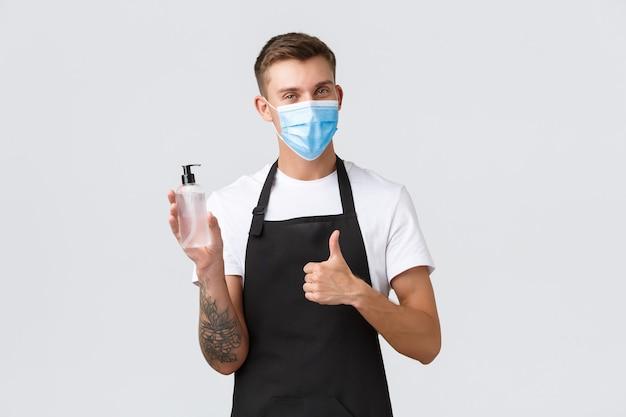 Coronavirus, distanciation sociale dans les cafés et restaurants, affaires pendant le concept de pandémie. un vendeur joyeux dans une épicerie, un barista ou un serveur montre le pouce levé et un désinfectant pour les mains pour la désinfection