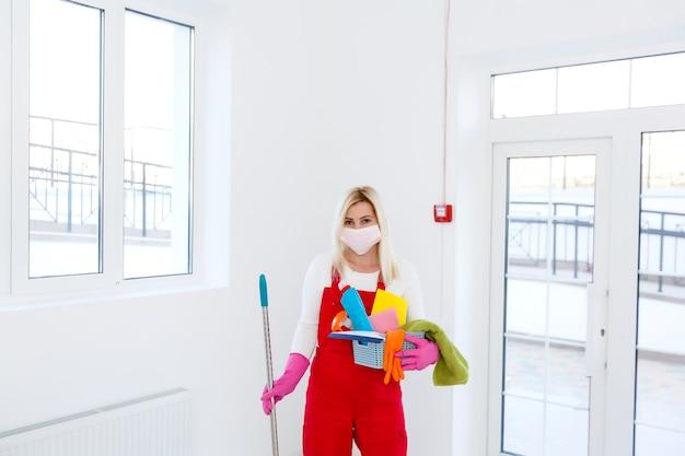 Coronavirus. femme avec masque facial nettoyant et désinfectant sa maison pendant l'épidémie de coronavirus. prévention de l'infection au covid-19. empêchez le coronavirus de se propager.