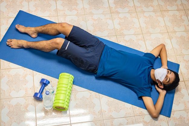 Coronavirus, homme asiatique porter un masque et faire de l'exercice seul dans la chambre à la maison pour prévenir covid-19. séance d'entraînement à domicile, exercice à domicile.