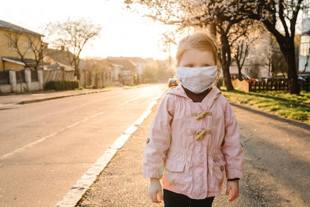 Coronavirus et maladies épidémiques virales. enfant en bonne santé dans un masque de protection médical dans la rue. protection et prévention de la santé pendant la grippe et les flambées infectieuses. restez à la maison pour vous sauver la vie.