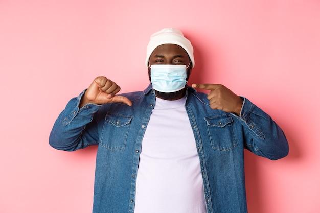 Coronavirus, mode de vie et concept de pandémie mondiale. un hipster mécontent pointant sur un masque facial, montrant les pouces vers le bas, n'aime pas le porter, fond rose.