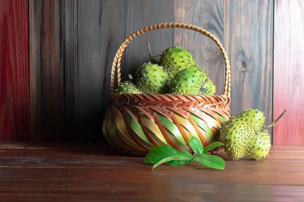 Corossol dans le panier ou la crème épineuse apple ou annona muricata l sur la table en bois