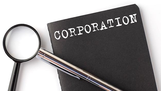Corporation, loupe avec message texte blanc sur le cahier noir
