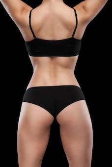 Corps athlétique sexy de femme, isolé sur fond noir.