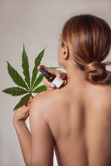 Le corps de la belle femme avec de l'huile liquide cbd à base d'extrait de cannabis. le dos nu d'une femme avec une feuille de cannabis. isolé sur fond gris