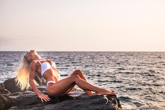 Corps bronzé et fitness séduisante jeune femme blonde prenant le soleil sur les rochers près de l'océan. activité de loisirs d'été en plein air pour les belles filles en vacances profitant du soleil et de la liberté.