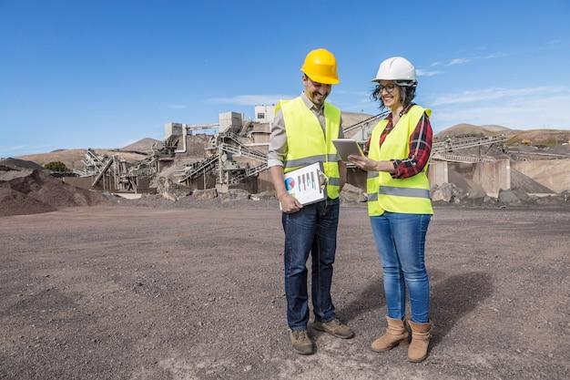 Corps complet de l'ingénieur femme positive montrant la tablette à un collègue masculin et expliquant les détails du projet lors de la visite du site de construction industrielle ensemble