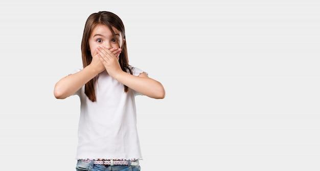 Corps complet, petite fille couvrant la bouche, symbole du silence et de la répression, essayant de ne rien dire