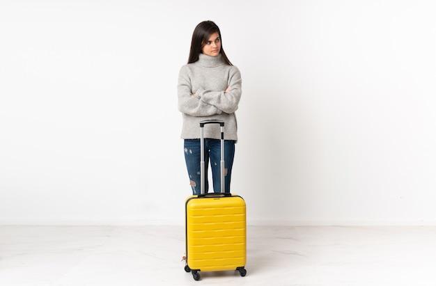 Un corps entier d'une femme voyageur avec une valise sur un mur blanc isolé pensant une idée