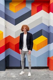 Corps entier de jeune homme au gingembre confiant contemporain avec des cheveux bouclés vêtus de vêtements de style décontracté à la mode, tout en se tenant debout contre un mur multicolore avec ornement géométrique
