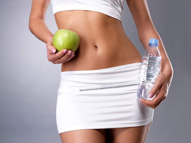 Corps de la femme en bonne santé avec pomme et bouteille d'eau. remise en forme saine et concept de mode de vie alimentaire.