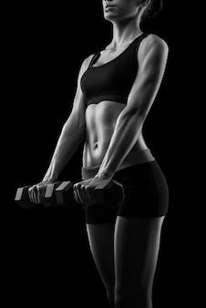 Corps de femme fitness sexy jeune sport avec des haltères posant sur fond noir, isolé. photographie en noir et blanc.