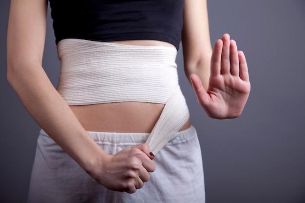 Corps de fille fort avec un bandage élastique sur les abdominaux
