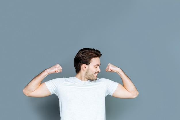 Corps fort. heureux bel homme bien construit souriant et regardant ses muscles tout en se sentant joyeux au sujet de sa force