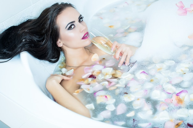 Corps de la jeune femme nue sensuelle dans le bain fille sexy se détendre dans la baignoire séduisante jeune femme brune sensuelle avec tenant un verre de vin couché dans une baignoire pleine d'eau avec de la mousse et des pétales de fleurs de rose