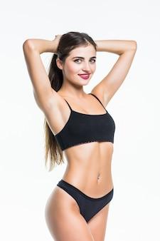 Corps mince de jeune femme en bikini noir. fille avec une figure sportive saine sur un mur blanc