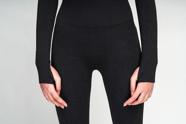 Corps mince parfait, ventre élastique et peau saine. femme sportive en haut et pantalon noirs, montrant sa silhouette en forme après l'entraînement sportif. motivation pour un grand concept de corps
