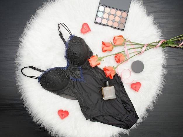 Corps noir, roses orange, rouge à lèvres, parfums et fard à paupières.