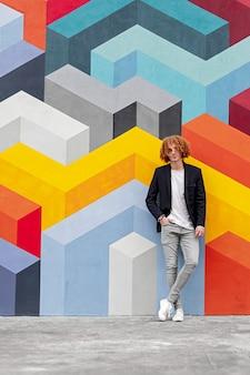 Corps plein de jeune homme élégant et confiant au gingembre aux cheveux bouclés en tenue décontractée à la mode tenant la main dans la poche et à la recherche, tout en se tenant près du mur avec un ornement géométrique multicolore