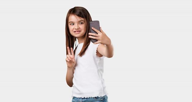 Corps plein petite fille confiante et gaie, prenant un selfie, regardant le mobile avec un geste drôle et insouciant, surfant sur les réseaux sociaux et internet