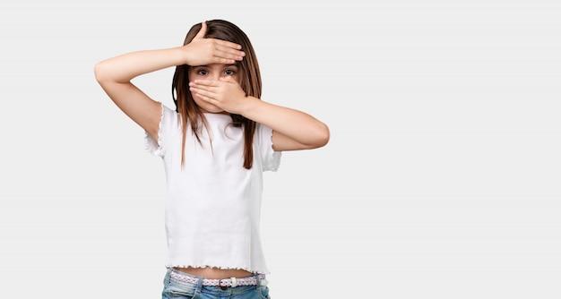 Corps plein de petite fille regardant à travers une brèche, se cachant et louchant
