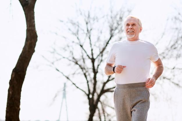 Corps sain. faible angle de l'homme mûr attrayant qui court dans le parc tout en contrôlant la respiration