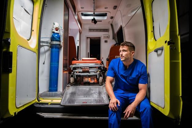 Corpsman en uniforme bleu assis dans une ambulance pensant
