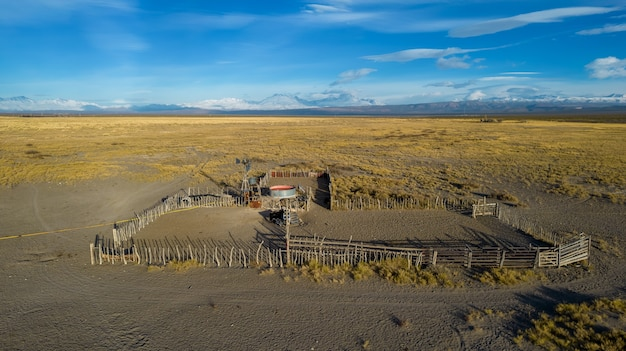 Corral d'animaux en patagonie argentine, avec un moulin à eau et des montagnes en arrière-plan.