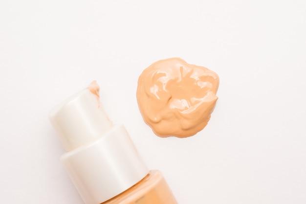 Correcteur liquide beige clair et frottis crème sur fond blanc. mise au point sélective.