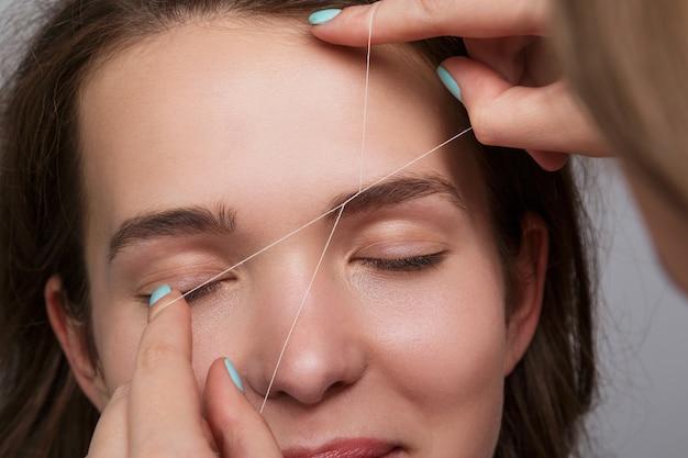 Correction des sourcils avec un fil blanc