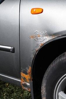 Corrosion de la voiture. rouille, peinture grise corrodée sur l'aile avant de la voiture. photo verticale.