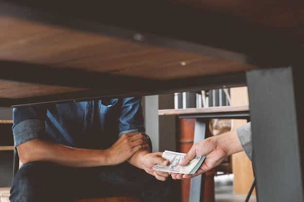 La corruption, les mains qui passent de l'argent sous table, les concepts de corruption et de corruption.