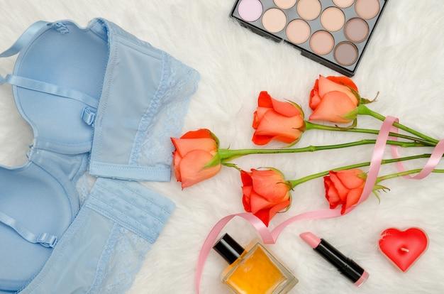 Corsage bleu avec dentelle, vue intérieure. fourrure blanche, roses oranges et cosmétiques