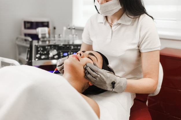 Cosmelotologist fait un massage facial stimulant avec des gants électriques.