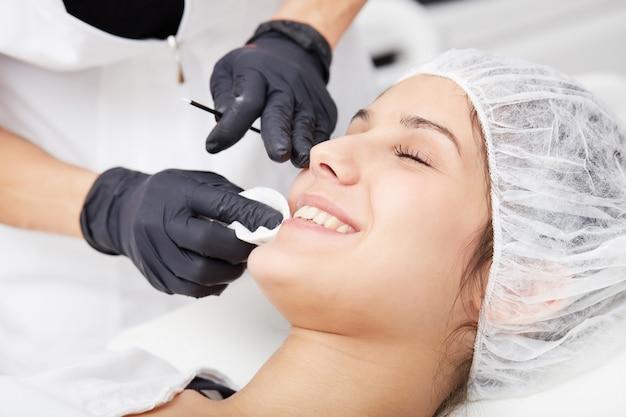 La cosméticienne applique un maquillage permanent sur les lèvres