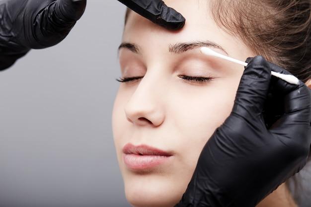La cosméticienne applique un maquillage permanent sur les sourcils