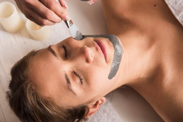 Cosméticienne appliquer masque sur le visage de la femme