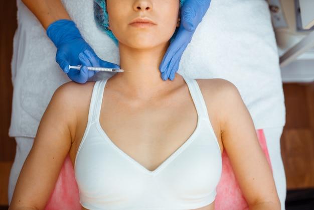 La cosméticienne donne une injection de botox contre les rides