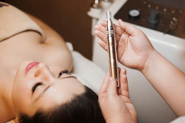 Cosméticienne mains tenant un dispositif à micro-aiguille pour les procédures de microdermabrasion non invasives du visage.