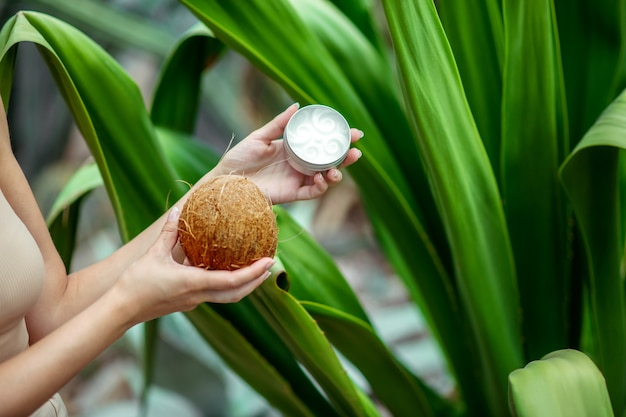 Cosmétique bio. gros plan des mains de femme tenant une noix de coco et un pot de crème