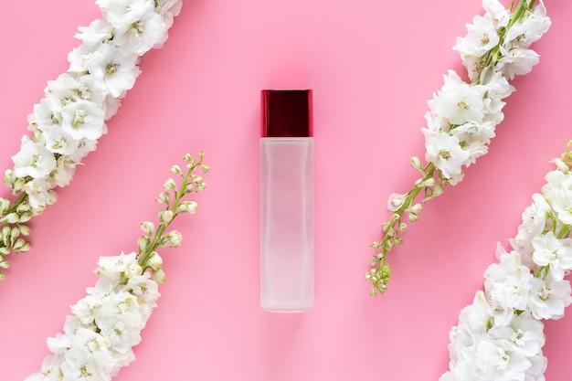 Cosmétique de luxe maquette bouteille contenant avec une fleur de printemps blanc à base de plantes