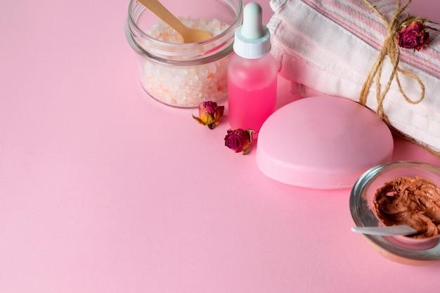 Cosmétique de soin du visage avec gommage bio, masque, savon et huile de rose sur fond rose avec une serviette