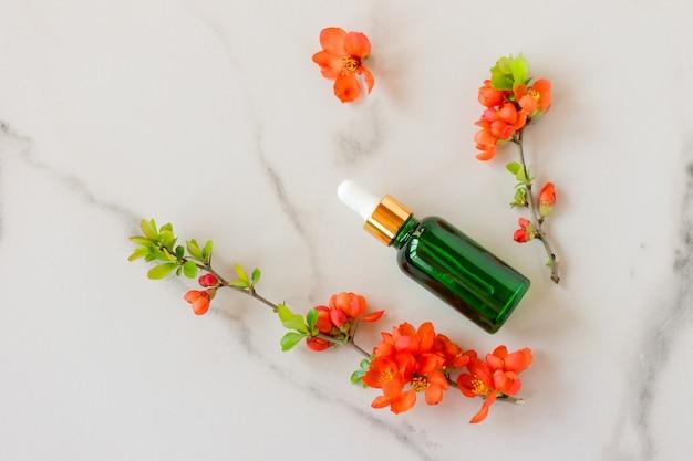 Cosmétique spa bio avec des ingrédients à base de plantes. sérum aux extraits de plantes pour les soins de la peau. cosmétiques nature dans une bouteille en verre avec une pipette et des fleurs sur fond de marbre.