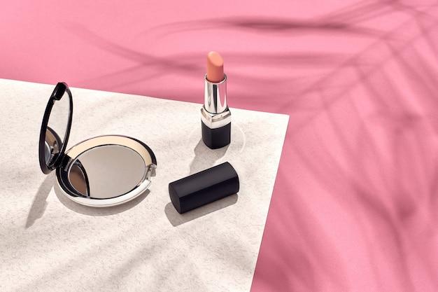Cosmétiques et accessoires pour femmes à la mode à plat ombre de fond rose et blanc d'une feuille de palmier