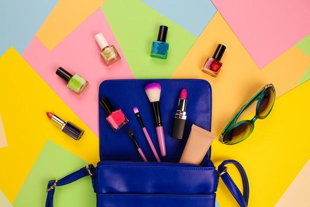 Les cosmétiques et les accessoires pour femmes sont tombés du sac à main bleu