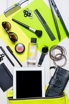 Les cosmétiques et les accessoires pour femmes sont tombés du sac à main vert sur fond blanc