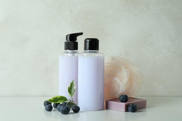 Cosmétiques de bain naturels et myrtille sur fond texturé blanc