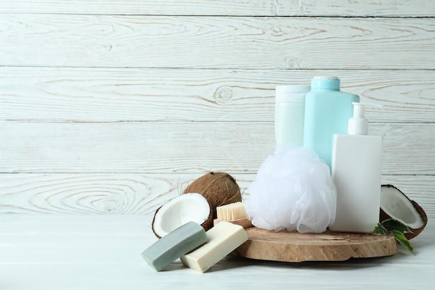 Cosmétiques de bain et noix de coco sur fond de bois blanc