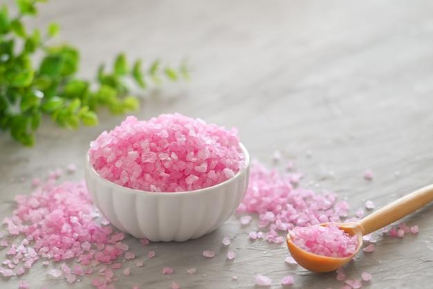 Cosmétiques à base de plantes close-up de sel de bain rose dans le bol en verre avec des bougies aromatiques avec copie espace